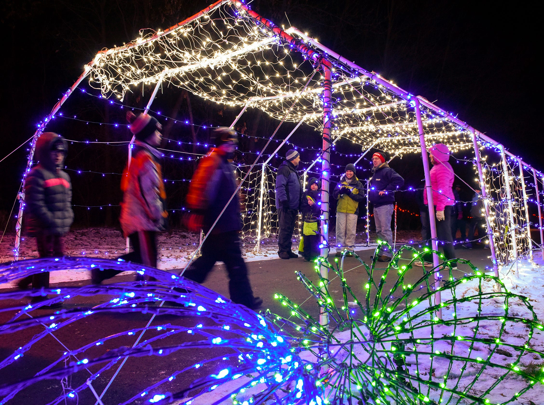 A steady stream of people arrive for the Country Lights Festival Friday, Dec. 7, in Sartell. The lighted trail circles Lake Francis Park behind the Sartell Community Center.