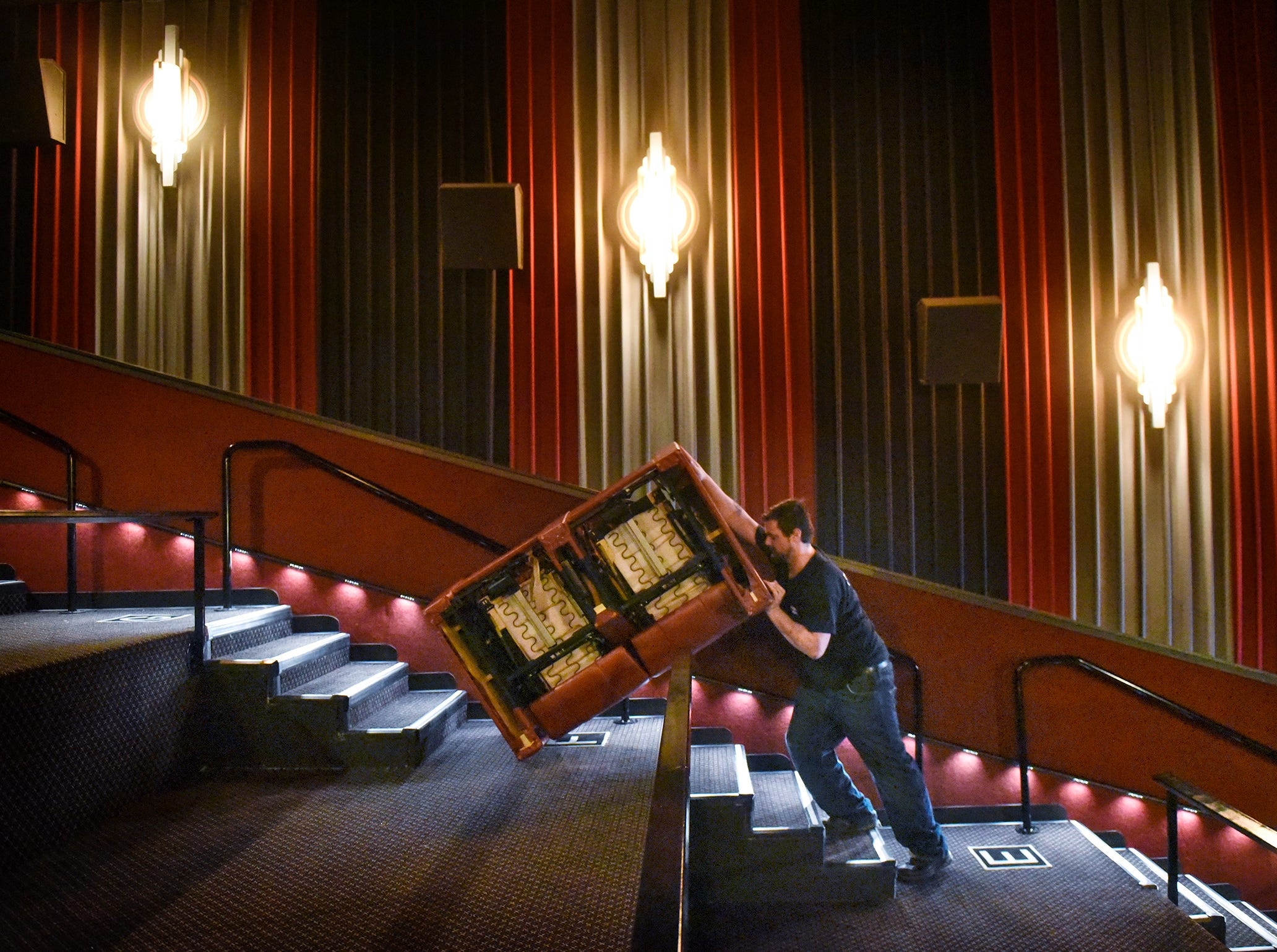 Michael Ferragina muscles a new DreamLounger recliner seat into place Wednesday, April 18, at Marcus Parkwood Cinema in Waite Park.