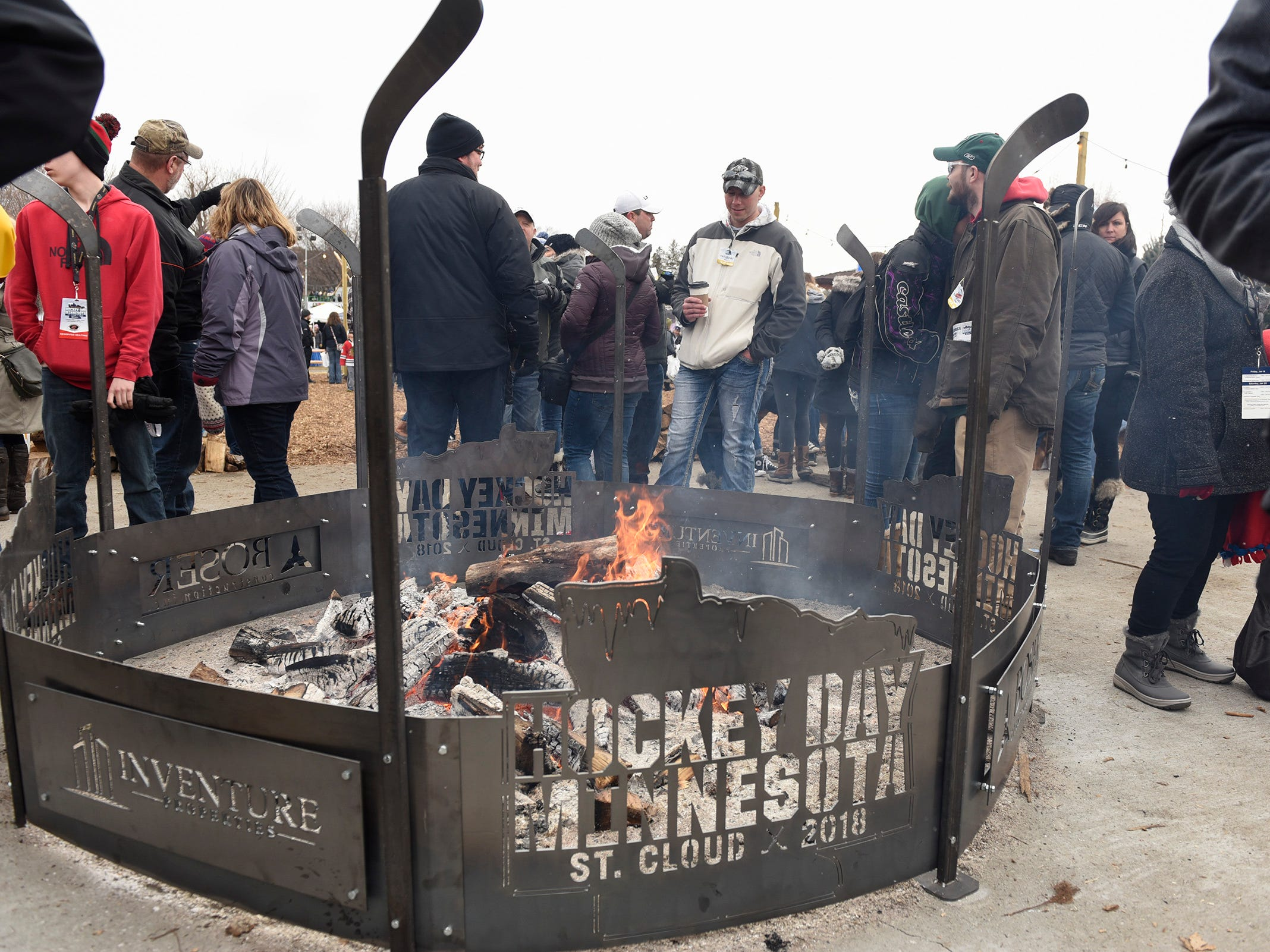 Fans talk by the fire pit Saturday, Jan. 20, during Hockey Day Minnesota at Lake George.