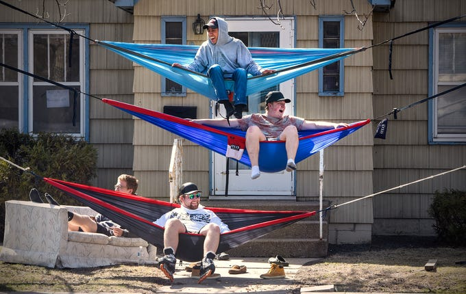 Cole Rau, Derek Mendel, Justin Hagstrom and Peyton Graf enjoy watching the world go by on a sunny afternoon Wednesday, April 23, from their perches on hammocks and a couch in their front yard along Ninth Avenue South in St. Cloud.