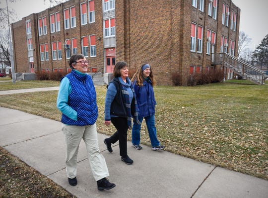 Glenda Burgeson, Jane Brown and Kaye Schimnich walk past the Wilson school building Wednesday, Dec. 19, which is located in their neighborhood.