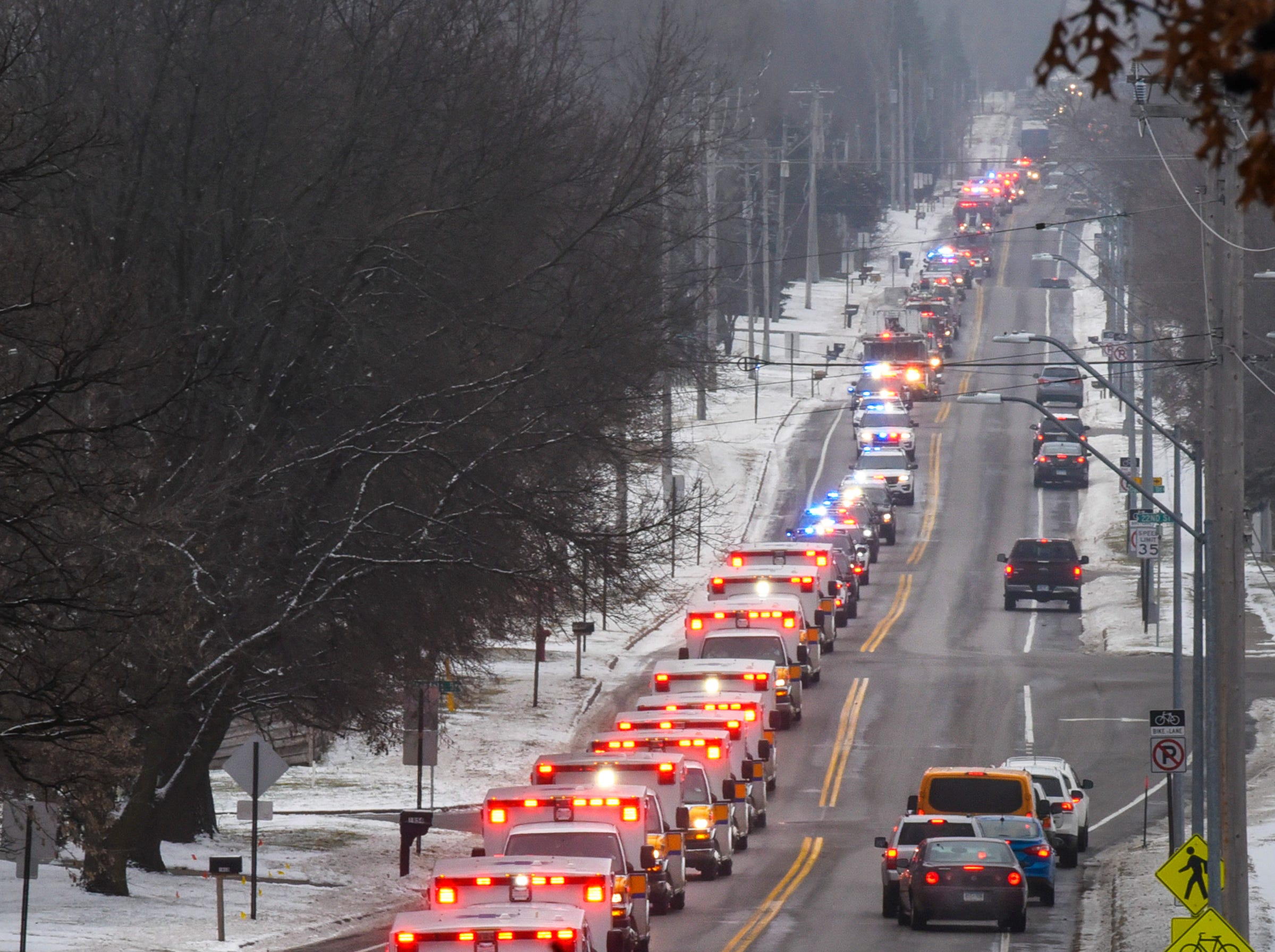 A long line of emergency vehicles forms a procession to honor paramedic Nicole Van Heel Friday, Nov. 30, along Cooper Avenue South following her funeral in St. Cloud. Van Heel died Nov. 25 from complications related to a stroke she suffered while on duty. Police, fire and EMS vehicles from agencies throughout the state participated in the procession and funeral.