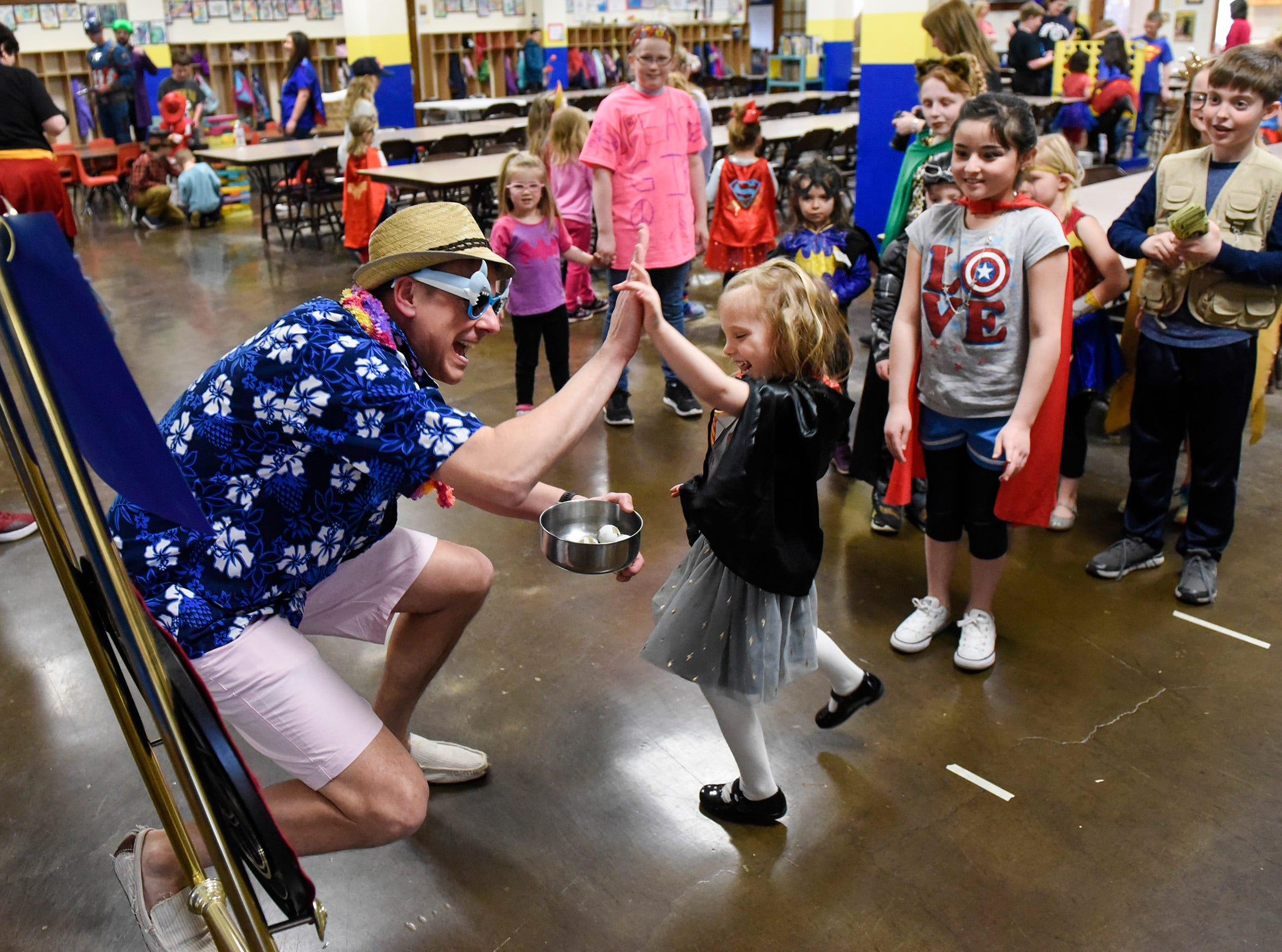 Students play the Captain America Shield Throw game with parent volunteer Matt Beirne during Superhero Day Friday, April 27, at All Saints Academy in St. Joseph. Money raised by the students will go to the Epilepsy Foundation.