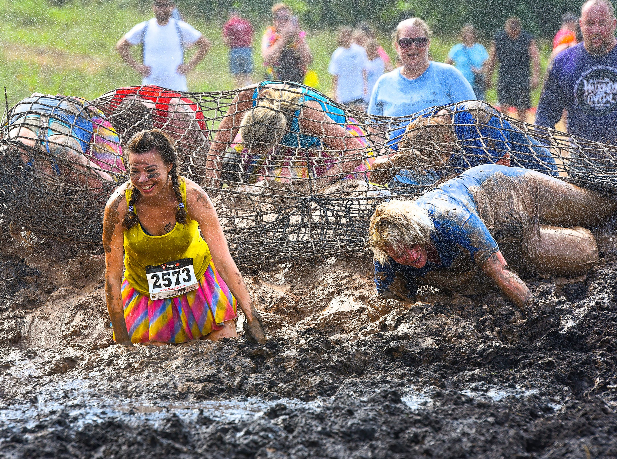 Runners crawl under the net through the water and mud in the Mudman Race Saturday, July 21, around Powder Ridge Recreation Area in Kimball. About 700 runners took the challenge to concur the 2k or 5k courses.