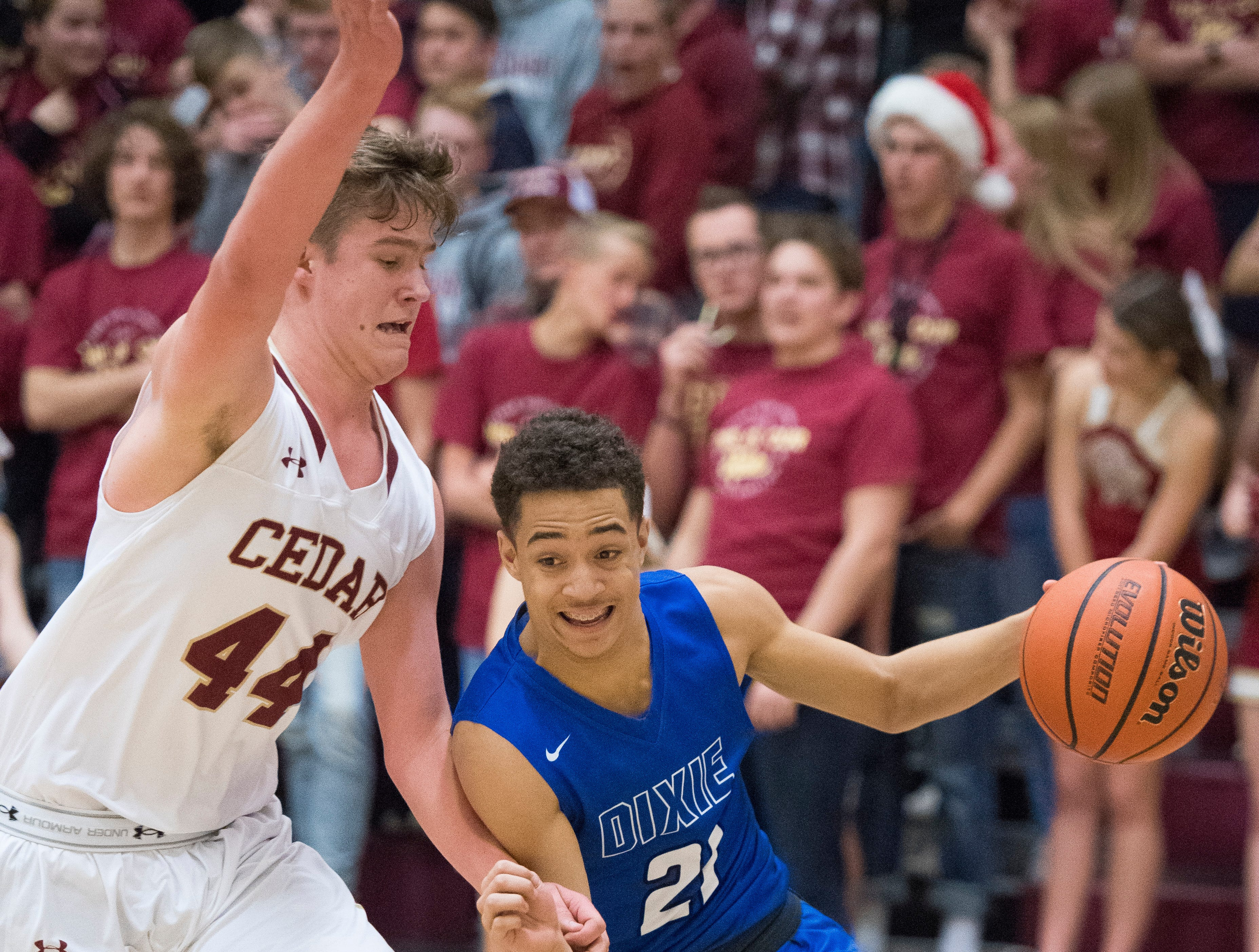 Dixie High School junior Christopher Schultz (21) works Cedar High School sophomore Luke Armstrong (44) at CHS Wednesday, December 19, 2018. Trading the lead all game, Dixie won, 49-45.