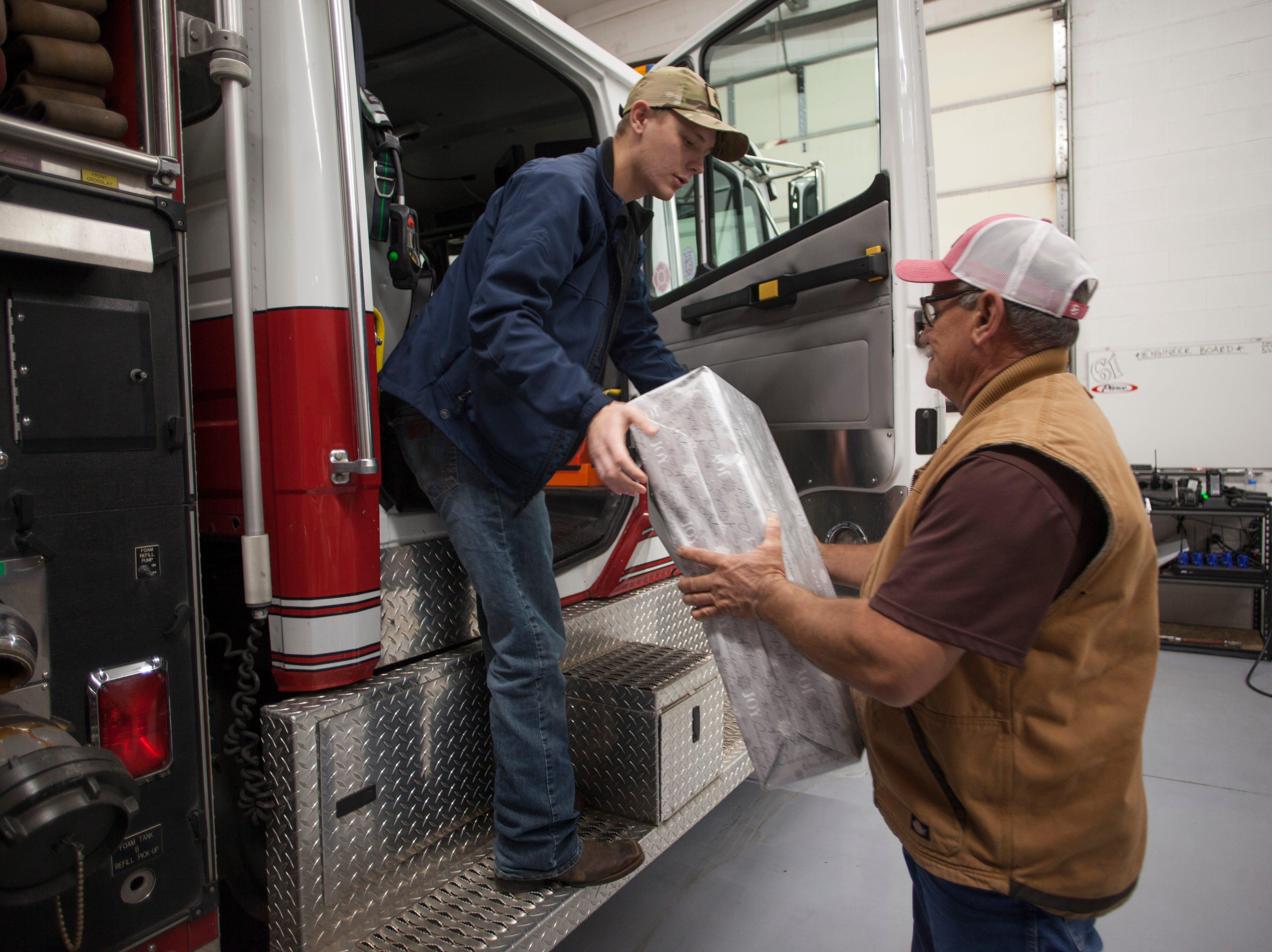 Members of the Washington Fire Department and community volunteers deliver gifts as part of the Angel Tree Project Wednesday, Dec. 19, 2018.