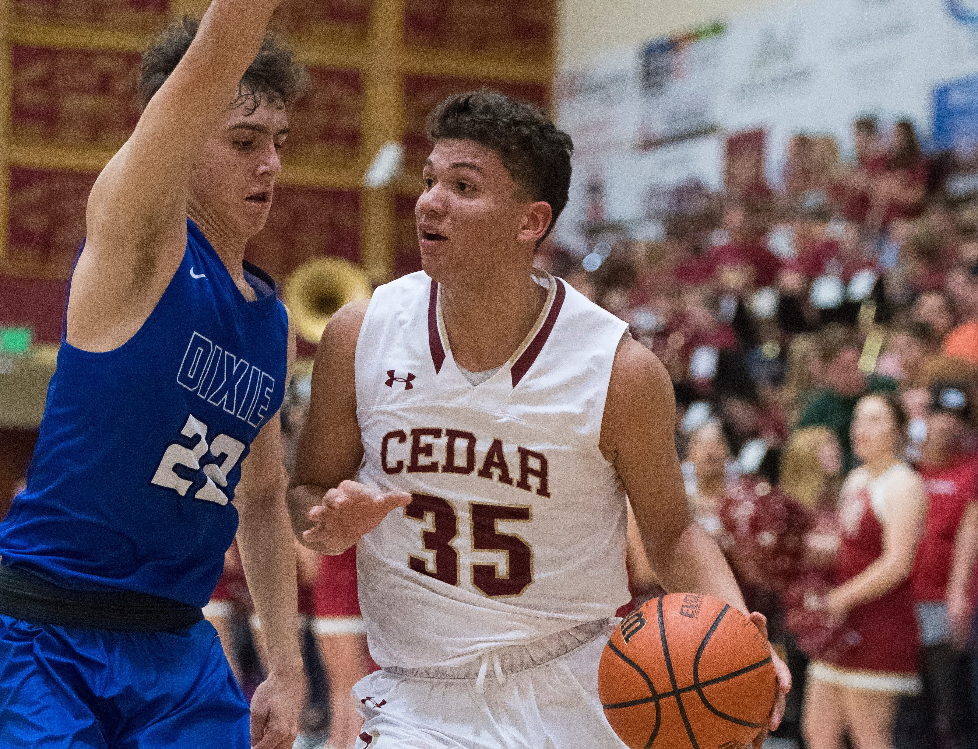 Cedar High School freshman Jorge Reyes (35) looks for passing options against Dixie at CHS Wednesday, December 19, 2018. Trading the lead all game, Dixie won, 49-45.