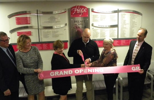 """Dr. Christopher """"Kit"""" Swiecki, general surgeon at Ascension St. Michael's Hospital, center, cuts the ribbon during a grand opening celebration on Oct. 25, 2018, for the Ascension St. Michael's Breast Care Center in Stevens Point. Also pictured, from left, are Hope is Building Campaign co-chairs Joe and Cindy Kinsella and Kim Hodgson, breast cancer survivor Felicia Van Lysal and campaign co-chair Steve Hodgson."""
