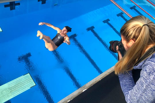 Democrat photographer Alicia Devine works on capturing a photo sequence of Chiles senior Rainey Vause diving at Morcom Aquatic Center.