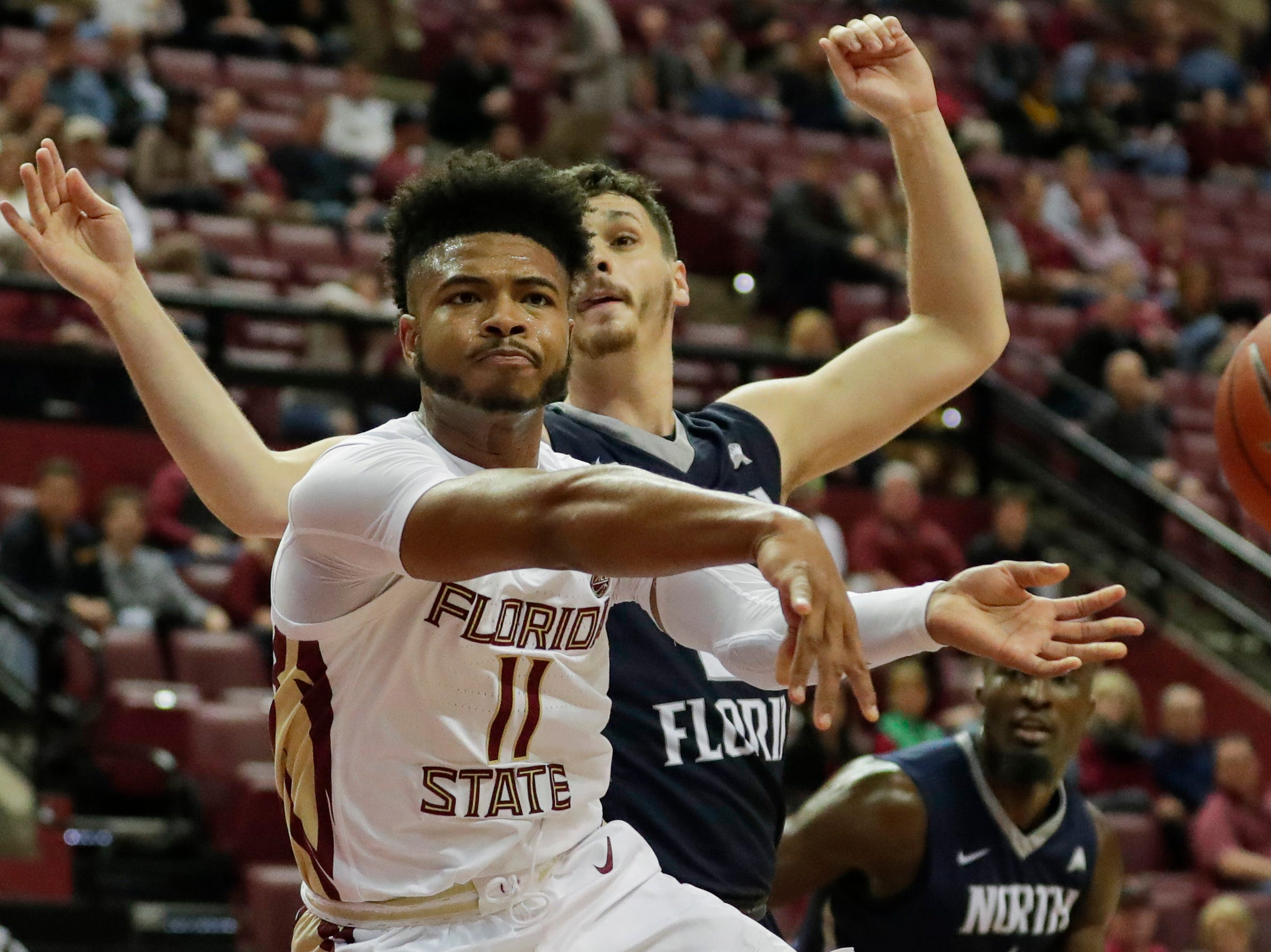 Florida State Seminoles guard David Nichols (11) makes a quick pass from under the hoop during a game between Florida State University and the University of North Florida at Donald L. Tucker Civic Center in Tallahassee, Fla. Wednesday, Dec. 19, 2018.