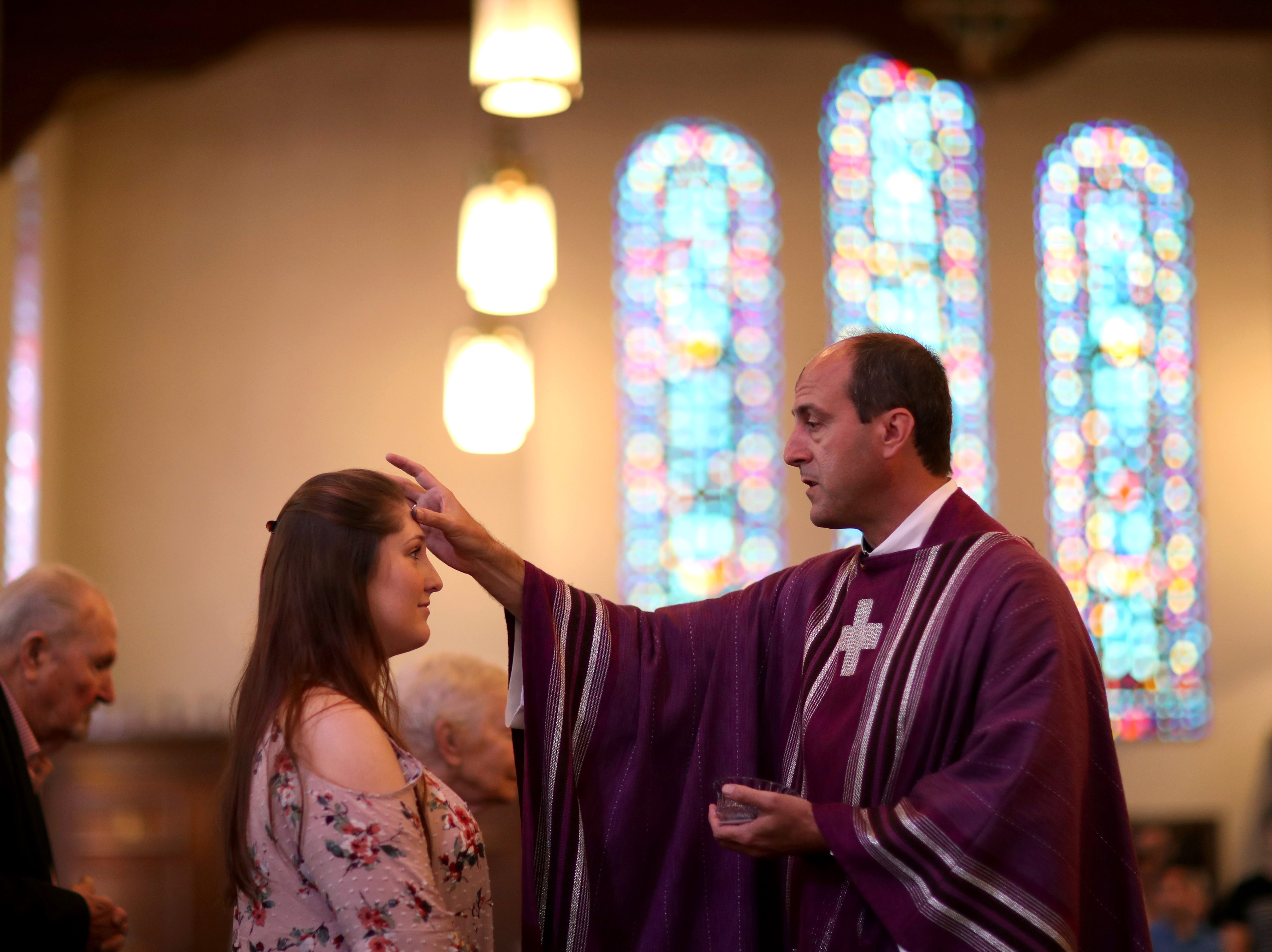 Sydney Sharp is marked with a cross by Father John Cayer during the Ash Wednesday ceremony at the Co-Cathedral of Saint Thomas More on Wednesday, Feb. 14, 2018.