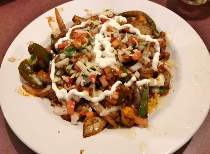 Casa Azteca's fajita bowl with rice, pinto beans, sautéed onions, peppers, grilled chicken, Pico de Gallo, shredded cheese and sour cream.