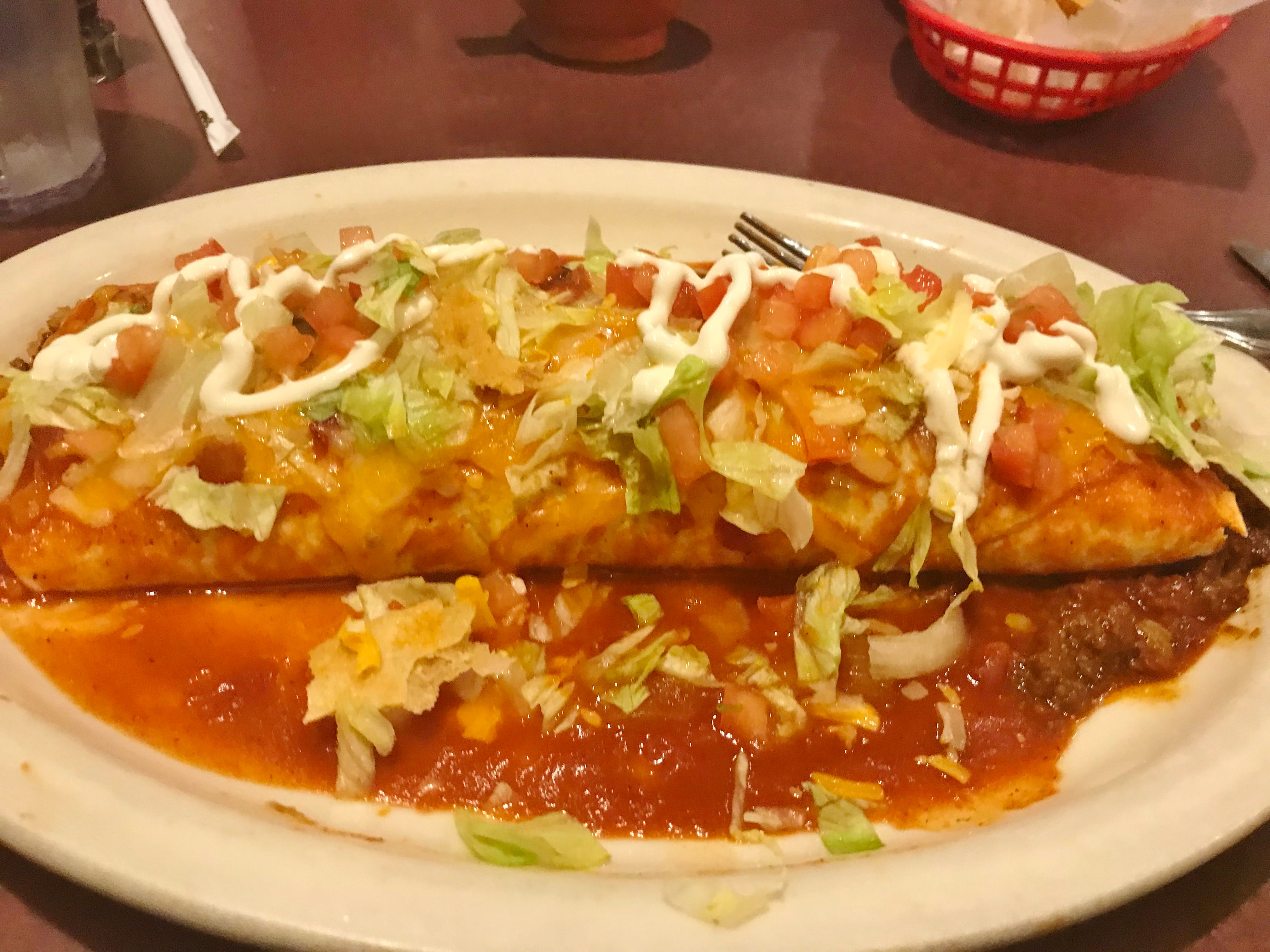 Casa Azteca's  Macho Burrito was a ginormous flour tortillafilled with rice, refried beans and marinated ground beef, smothered with Casa Azteca's famous burrito sauce and cheese then baked. It was garnished with chopped lettuce, tomatoes and sour cream.