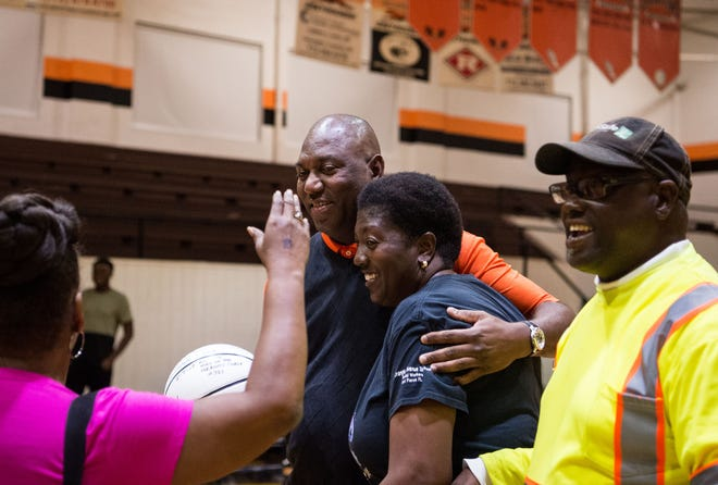 Lincoln Park Academy girls basketball head coach Wendell Adams (center) is hugged by his sister, Kim Adams, as supporters surround him to celebrate his 400th career win after their game against Port St. Lucie on Wednesday, Dec. 19, 2018, at Lincoln Park Academy in Fort Pierce.