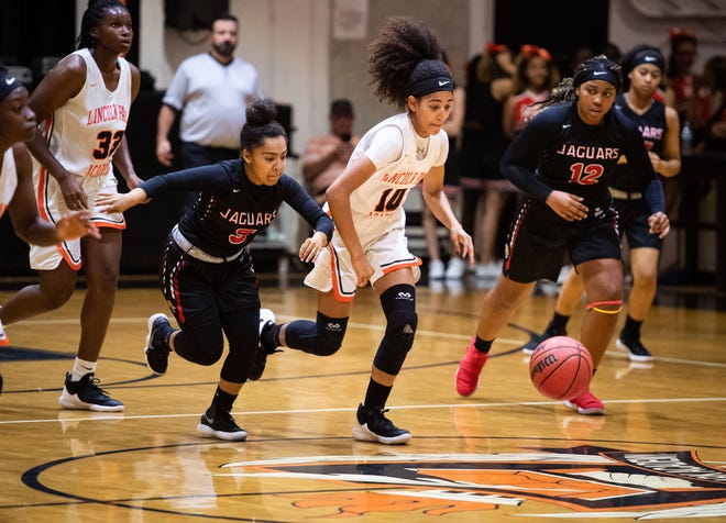 Lincoln Park Academy's Christen McCann (center) breaks downcourt after stealing the ball as Port St. Lucie players Aaliyah Brand (left) and Iyani Mutakbbir pursue her during the second period of the high school girls basketball game Wednesday, Dec. 19, 2018, at Lincoln Park Academy in Fort Pierce.