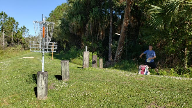 Roger Jacobsen of Fort Pierce makes an attempt at scoring par on the disc golf basket on the 6th hole at the disc golf course at Halpatiokee Park in Martin County.