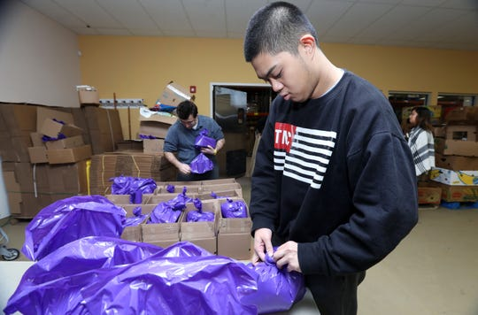 Joseph Petras, right, and Ross Macchia, both 22 and part of the Arc of Westchester Choices Neighborhood program, pack bags of nutritious foods for schoolchildren at Feeding Westchester, where they volunteer regularly, Dec. 19, 2018 in Elmsford. Many of Arc of Westchester's clients with developmental disabilities volunteer for a local non profits to build work and relationship skills as well as to give back to the community.