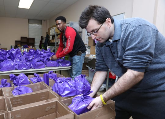 Ross Macchia, 22, with the Arc of Westchester Choices Neighborhood program, packs bags of nutritious foods for schoolchildren with Andrew Malson at Feeding Westchester, where he volunteers regularly, Dec. 19, 2018 in Elmsford. Many of Arc of Westchester's clients with developmental disabilities volunteer for a local non profits to build work and relationship skills as well as to give back to the community.