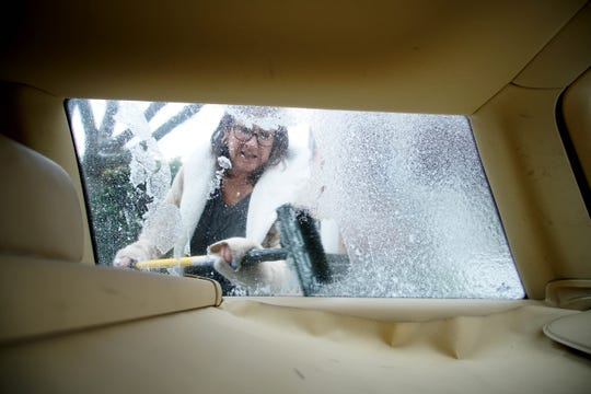 Lucy Conaty scraps ice off the windows of her car along Gilpin Avenue during a previous snow storm.