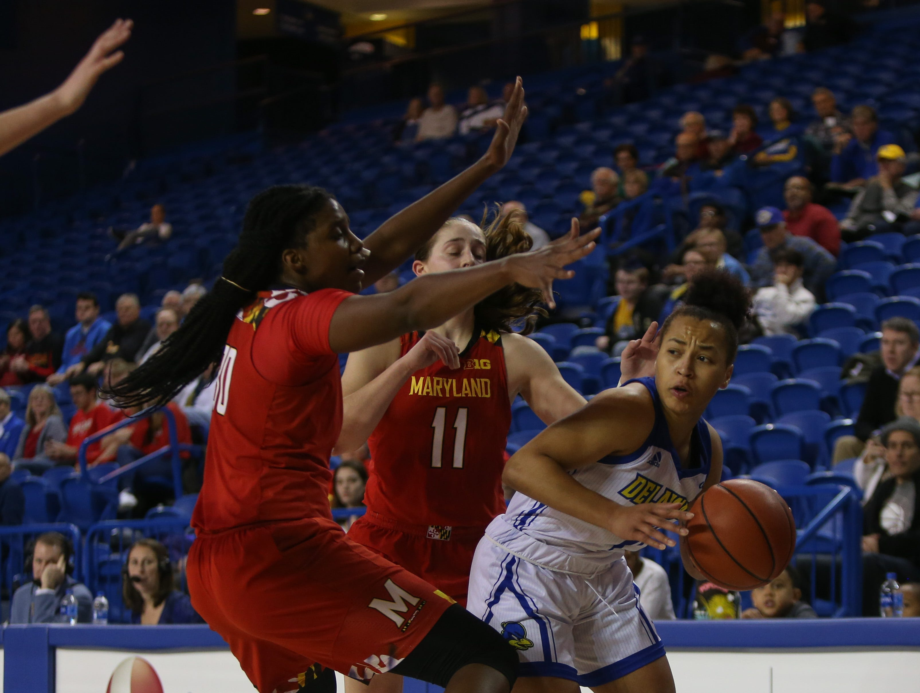 Delaware guard Paris McBride is swarmed by a pair of Maryland defenders. The University of Delaware women's basketball team falls to No. 5 University of Maryland 77-53 at the Bob Carpenter Center Thursday.