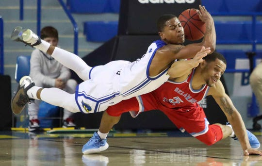 Delaware's Kevin Anderson (left) dives for the ball against Delaware State's Jon Mitchell in the first half at the Bob Carpenter Center Wednesday.