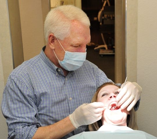 Wichita Falls private practice dentist Dr. John Thornton gives one of his dental assistants, Sonja Vines, an oral check-up before closing his private dental practice of more than 32 years.