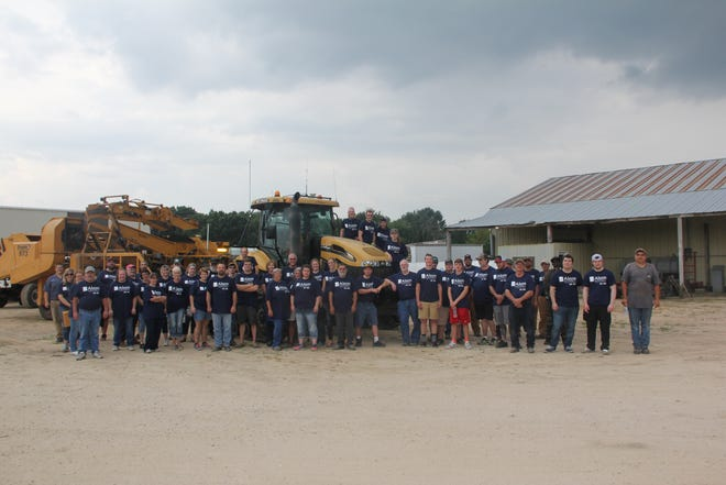 The Alsum Farms & Produce staff gather near potato harvest equipment.