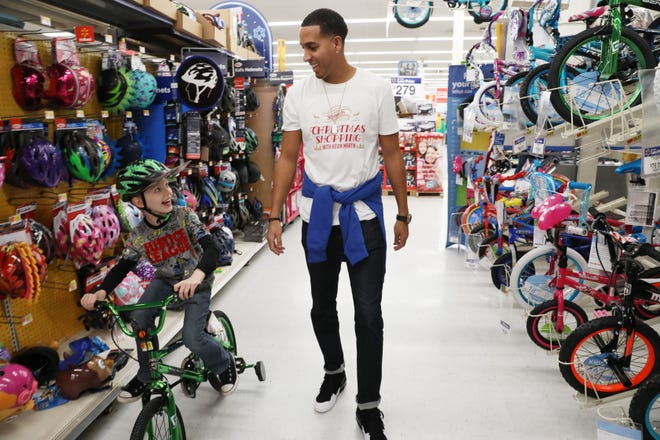 Retired NBA star and Zanesville native Kevin Martin chats with Myles Myers as Myers tries out a bike at Walmart in Zanesville during the annual Christmas Shopping with Kevin Martin event in 2018. COVID-19 prevented the shopping this year, but Martin still found a way to donate to needy families.