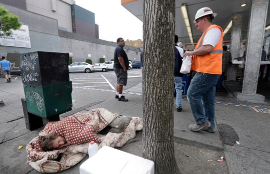 In this May 24, 2018, file photo, a man sleeps on the sidewalk as people behind line-up to buy lunch at a Dick's Drive-In restaurant in Seattle. A new federal report says the number of people living on the streets in Los Angeles and San Diego, fell this year. Meanwhile, homelessness overall was up slightly across the country, including Seattle.