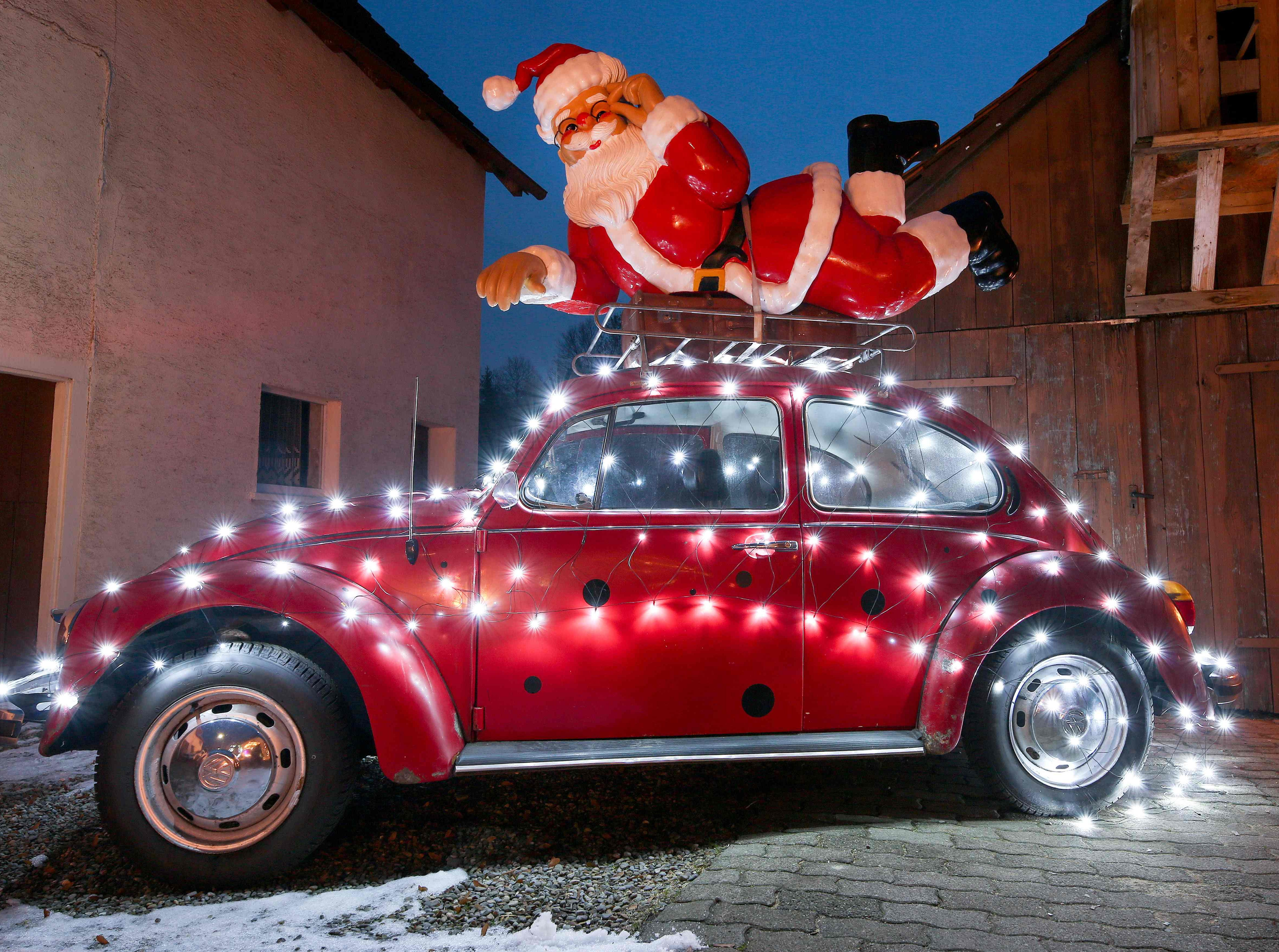 A Santa Claus sculpture is fixed on the roof rack of a Volkswagen Beetle vintage car decorated with a light chain on Dec. 19, 2018 in front of a house in Ertingen, southern Germany.