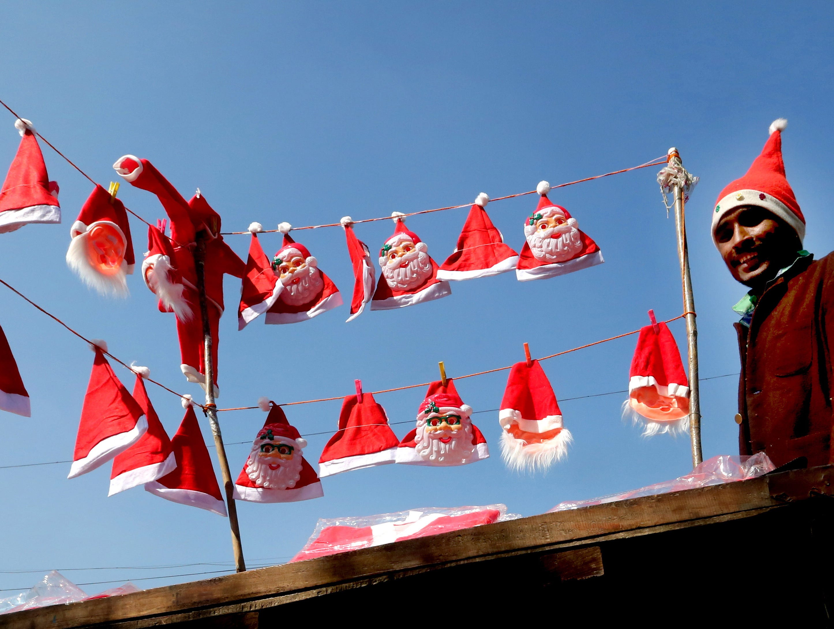 A roadside vendor sells Santa Claus caps and masks ahead of the Christmas festival in Bhopal, India on Dec. 19, 2018.