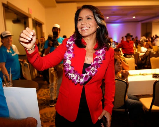File - In this Nov. 6, 2018, file photo, Rep. Tulsi Gabbard, D-Hawaii, greets supporters in Honolulu. Gabbard, Democratic congresswoman, is eyeing a White House run. The Iraq war veteran has visited New Hampshire and Iowa in recent months and has written a memoir that's due to be published in May. First elected to the state Legislature at age 21, Gabbard throughout her career has ignored suggestions that she wait her turn. (AP Photo/Marco Garcia, File)