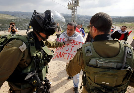 Israeli Border Police and army soldiers block Palestinian protesters from advancing near the southern West Bank village of Jab'a, in this 2015 file photo. The protesters carried posters referring to the BDS (Boycott, Divestment and Sanctions) movement which aims to put pressure on Israel to end its engagement in the Palestinian territories.
