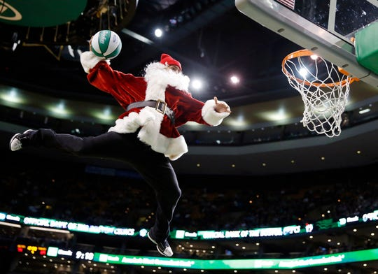 A performer in a Santa Claus costume goes up for a dunk.