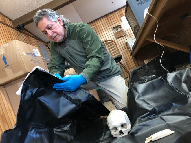 "Brooks County Sheriff Urbino ""Benny"" Martinez reviews the evidence sheet to a set of skeletal remains. The county recovers around 50 sets of remains a year, usually of migrants attempting to cross the U.S.-Mexico border."