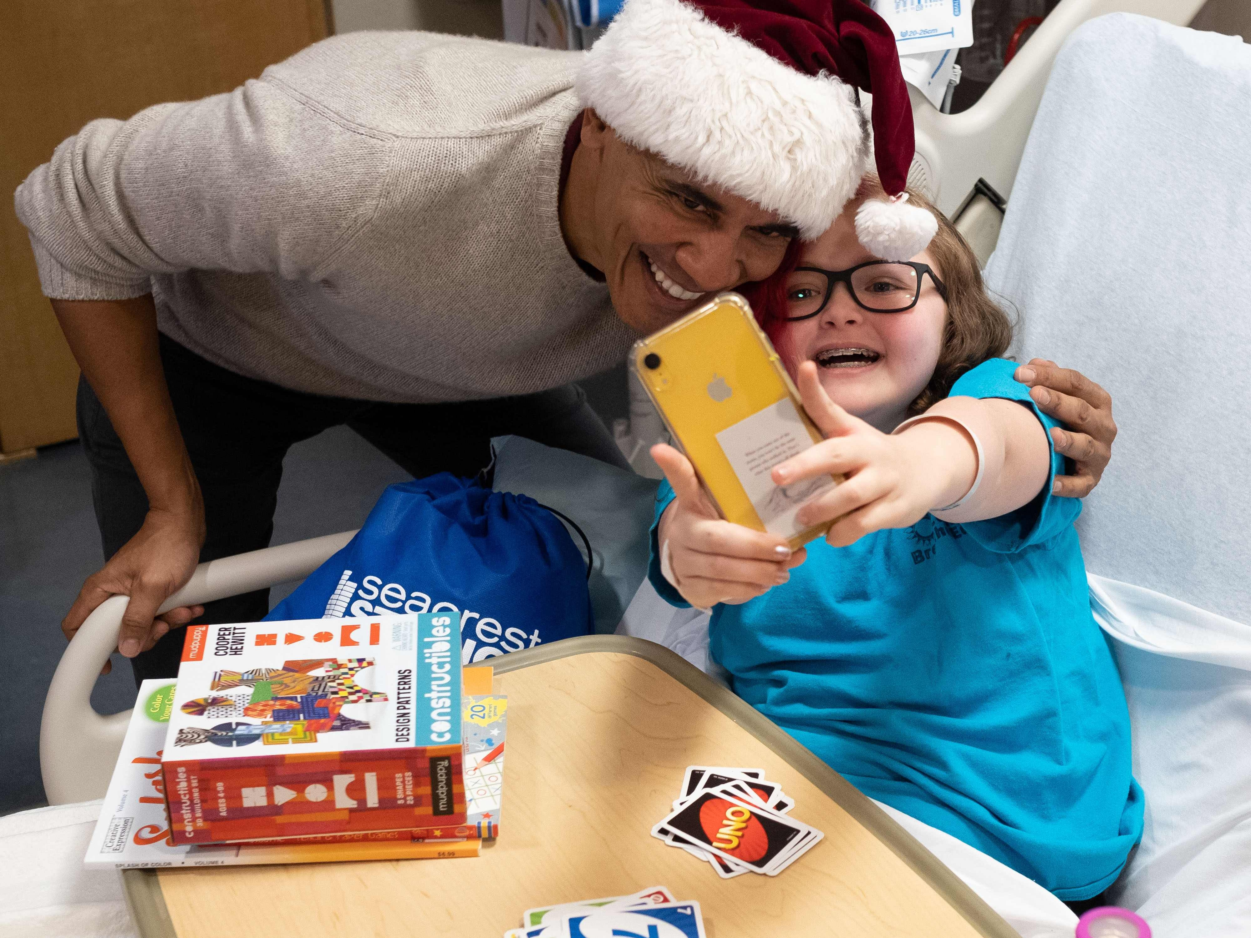 This photograph, obtained courtesy of the Obama Foundation, shows former President Barack Obama delivering gifts, greeting patients and their parents at Childrens National Medical Center in Washington, DC, Dec. 19, 2018.
