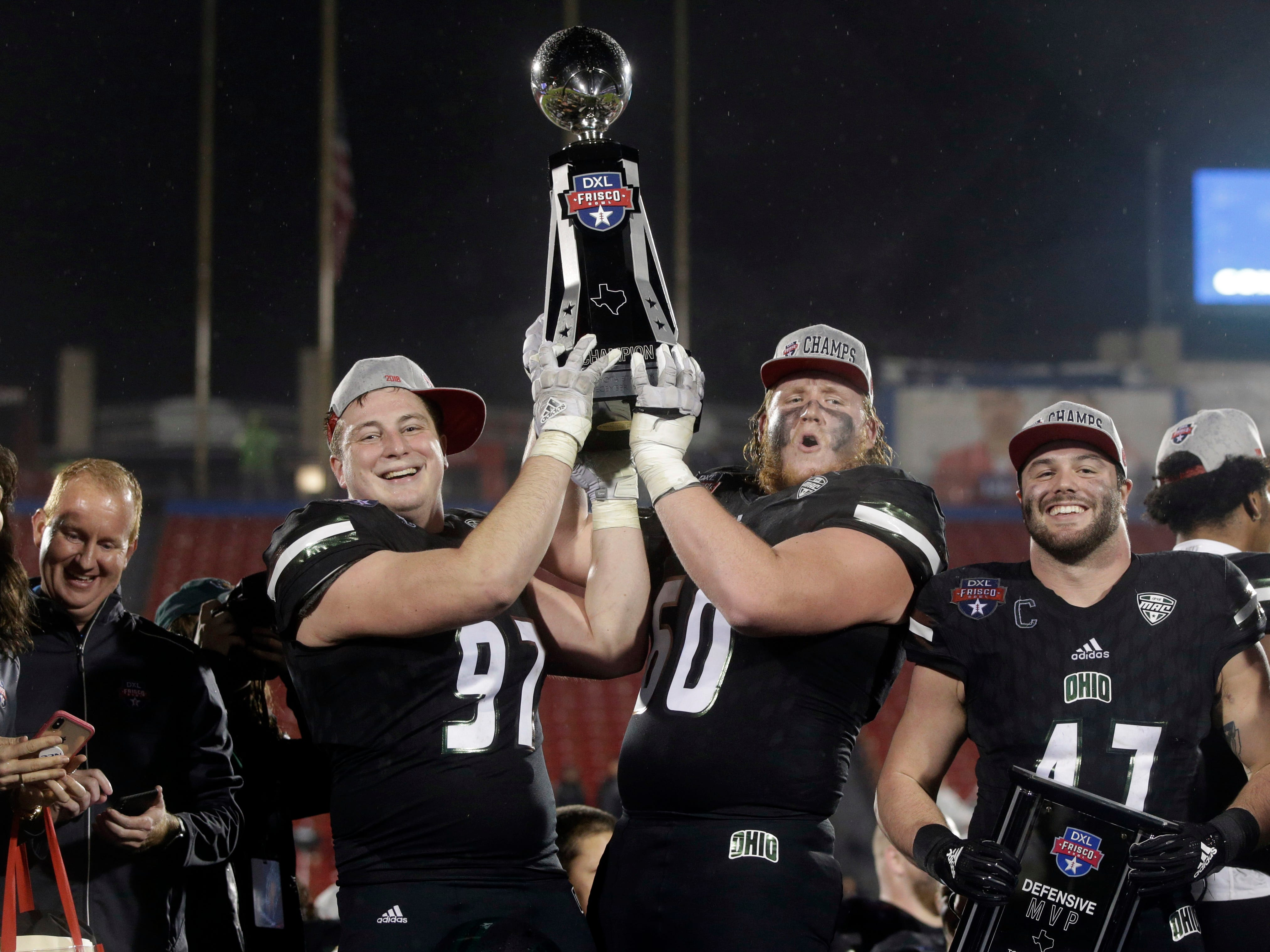 Ohio offensive lineman Austen Pleasants (60) and defensive lineman Kent Berger (97) hold up the trophy after winning the Frisco Bowl, 27-0, over San Diego State at Toyota Stadium.