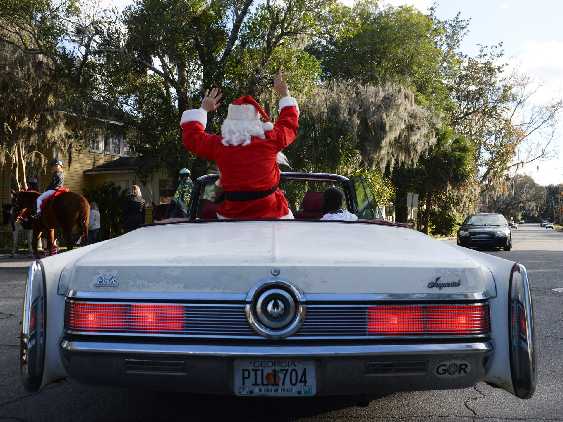Santa Claus cruises down Georgia Avenue in his backup sleigh, a Chrysler Imperial, during the Avondale Christmas Parade on Sunday, Dec. 16, 2018.