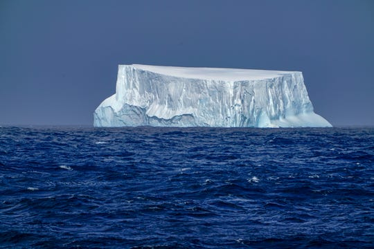 A blue-tinged iceberg, it's backside worn smooth by the waves, floats in the waters off Antarctica.