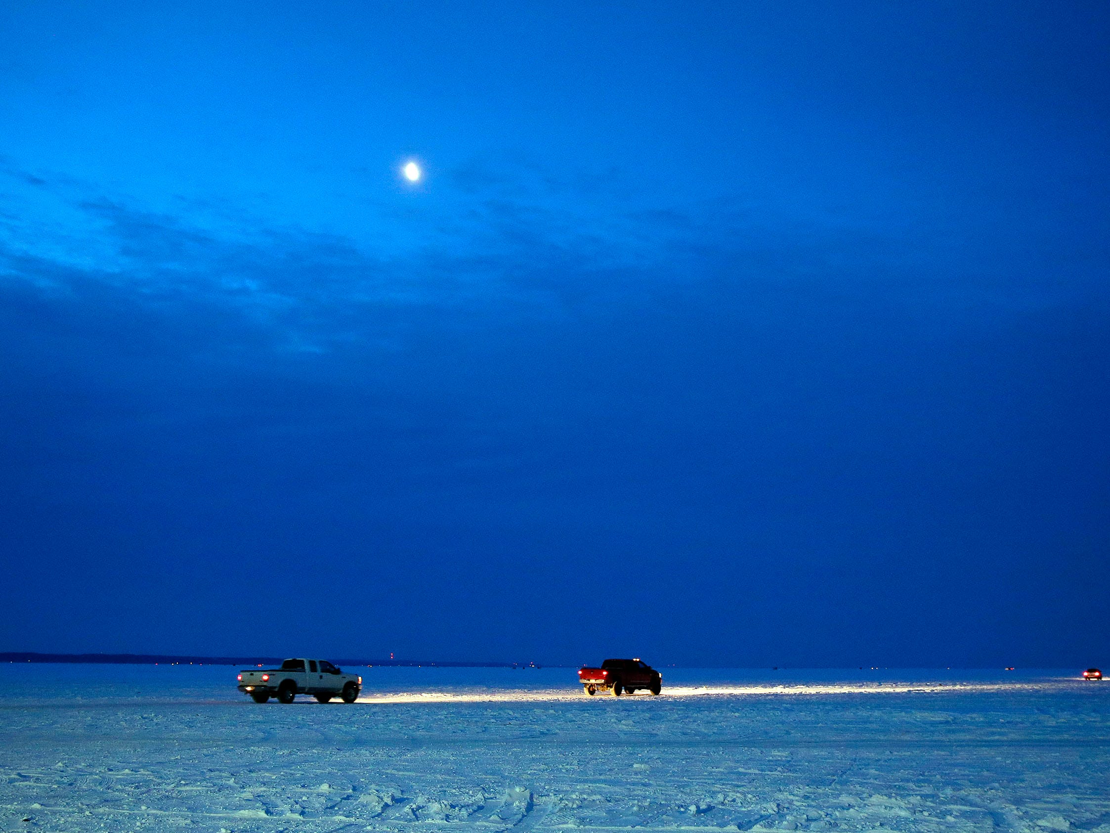 Trucks head across the ice before dawn as sturgeon season opens Saturday, February 10, 2018, on Lake Winnebago near Menasha, Wis.