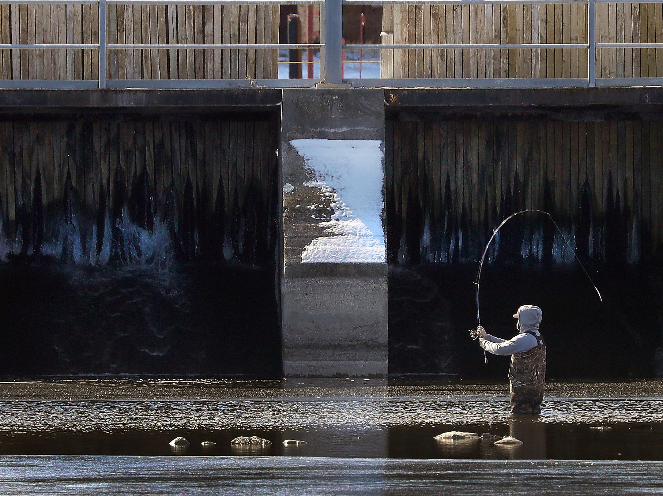 A man braves the cold water while fishing near the WG Bryan bridge on Thursday March 8, 2018 in Neenah, Wis. 