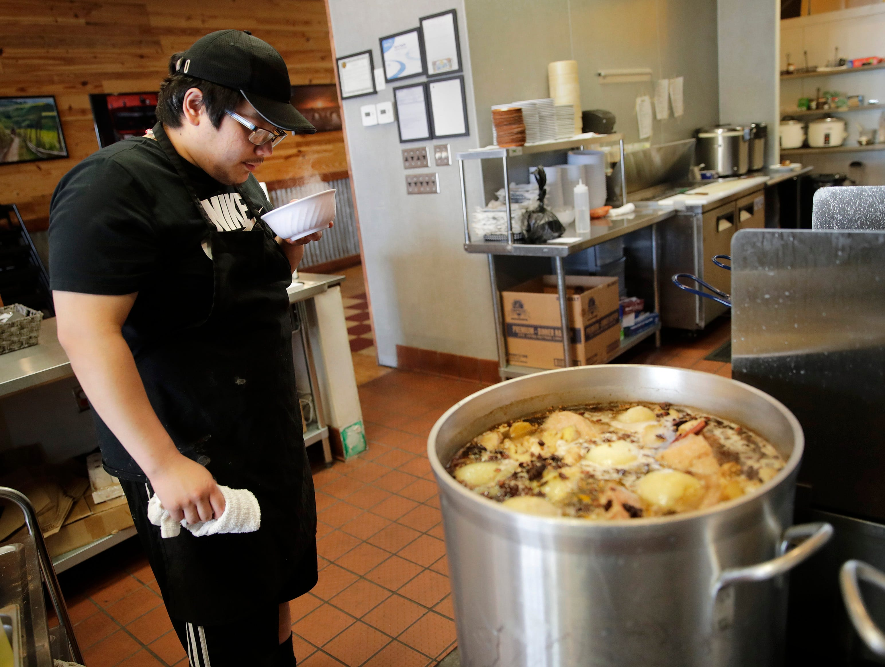 Lor Lee, owner of Rice Market Southeast Asian Kitchen, takes a sampling of his pho to make sure it has the correct amount of spices Tuesday, June 26, 2018, in Appleton, Wis.  Lee's mother Mai Vang runs Mai's Deli and his sister Yee Vue owns and operates Bowl Ninety-One.