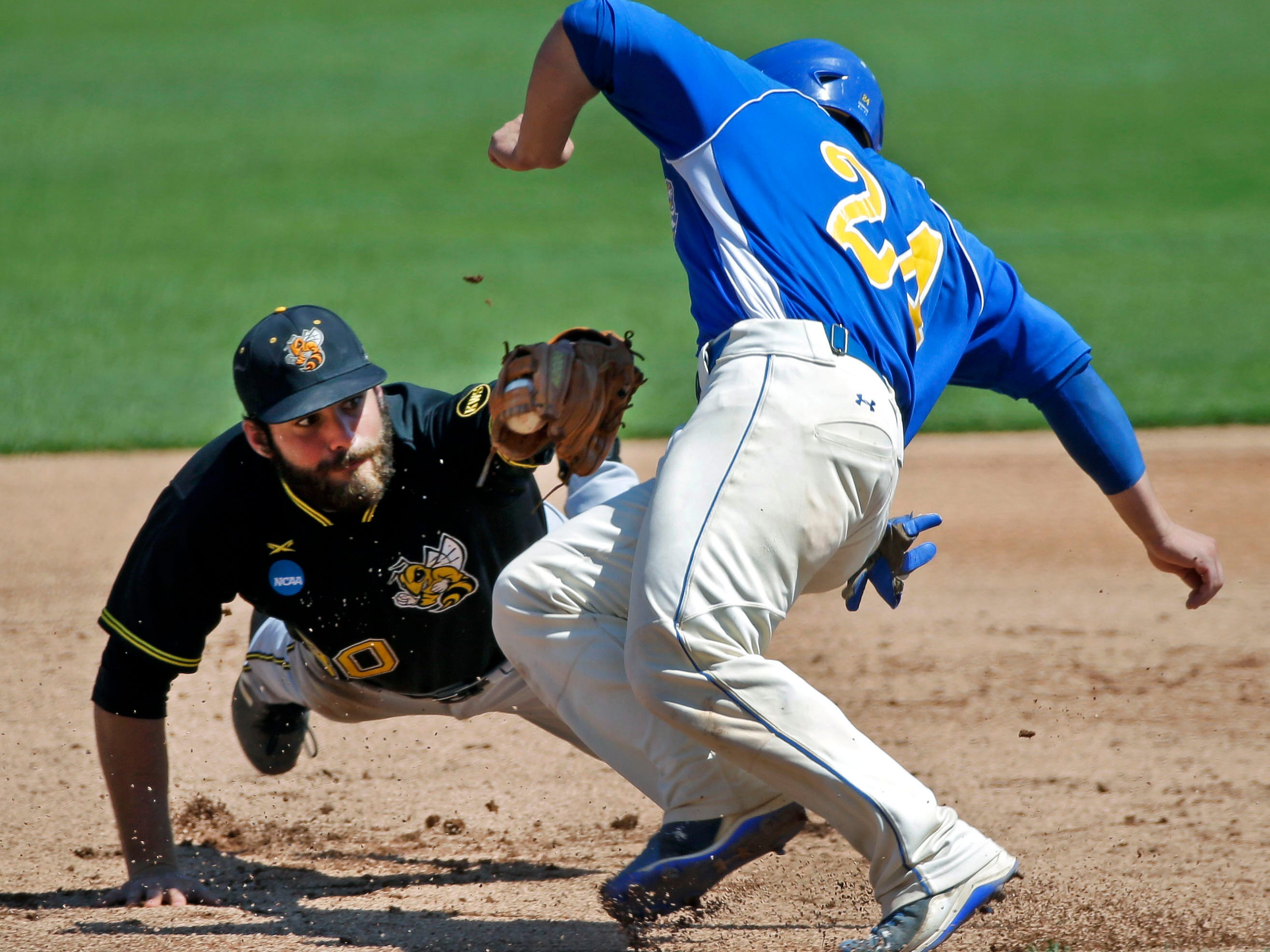 Santo Guinta of Misericordia University gets tagged at third by Michael Nickles of Randolph-Macon College Sunday, May 27, 2018, during the NCAA 2018 Division lll Baseball Championship at Neuroscience Group Field at Fox Cities Stadium in Grand Chute, Wis. The games continue through May 29.