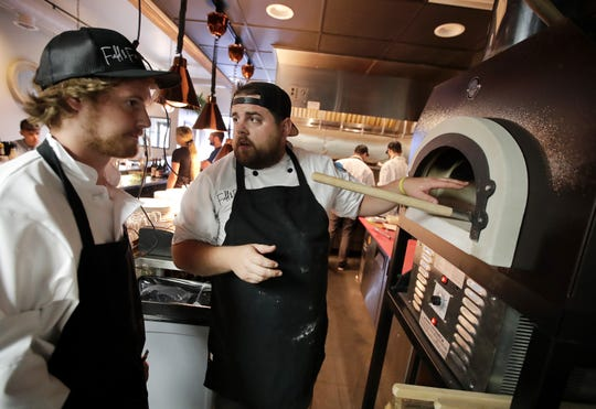Ryan Sherman, center, co-owner of Field & Fire, works with line chef Tim Novak.