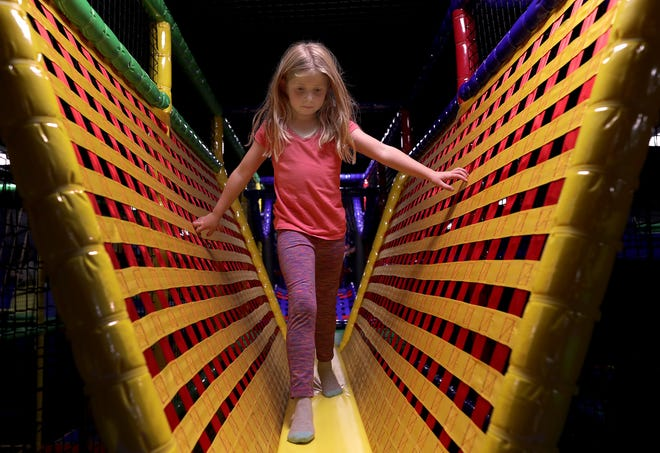 Makana Wohlt climbs on an indoor obstacle course at Luv2Play in Grand Chute.