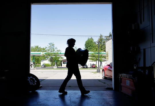 In this archived photo, an automotive technician replaces a wheel at JumpStart Auto in Neenah.