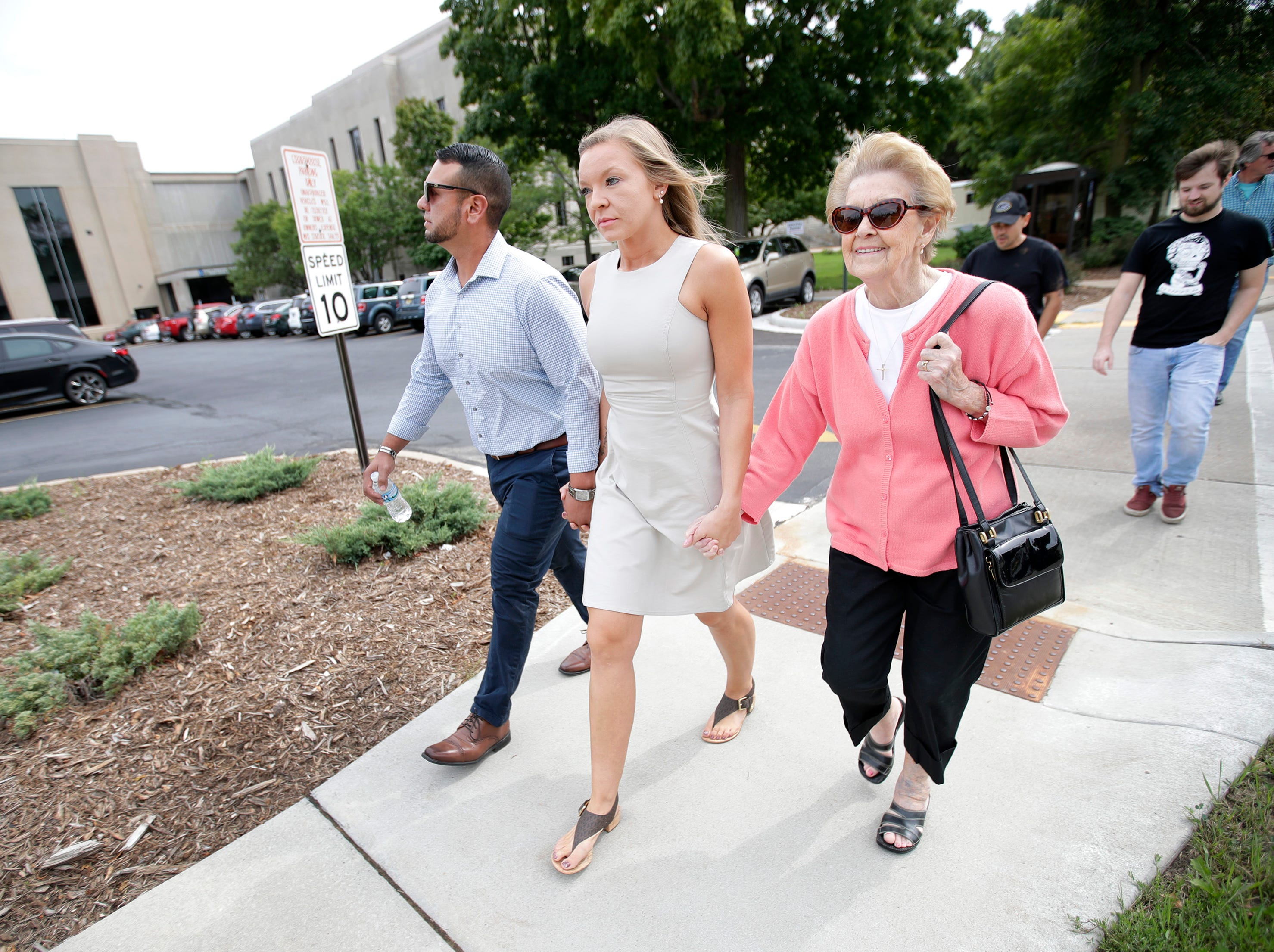 Natalie Coenen, of Appleton, walks hand in hand with her boyfriend Bruo Perez, of Appleton, and grandmother Betty Wilke, of Appleton, as she heads to her plea hearing at the Outagamie County Justice Center Friday, Sept. 7, 2018, in Appleton, Wis.