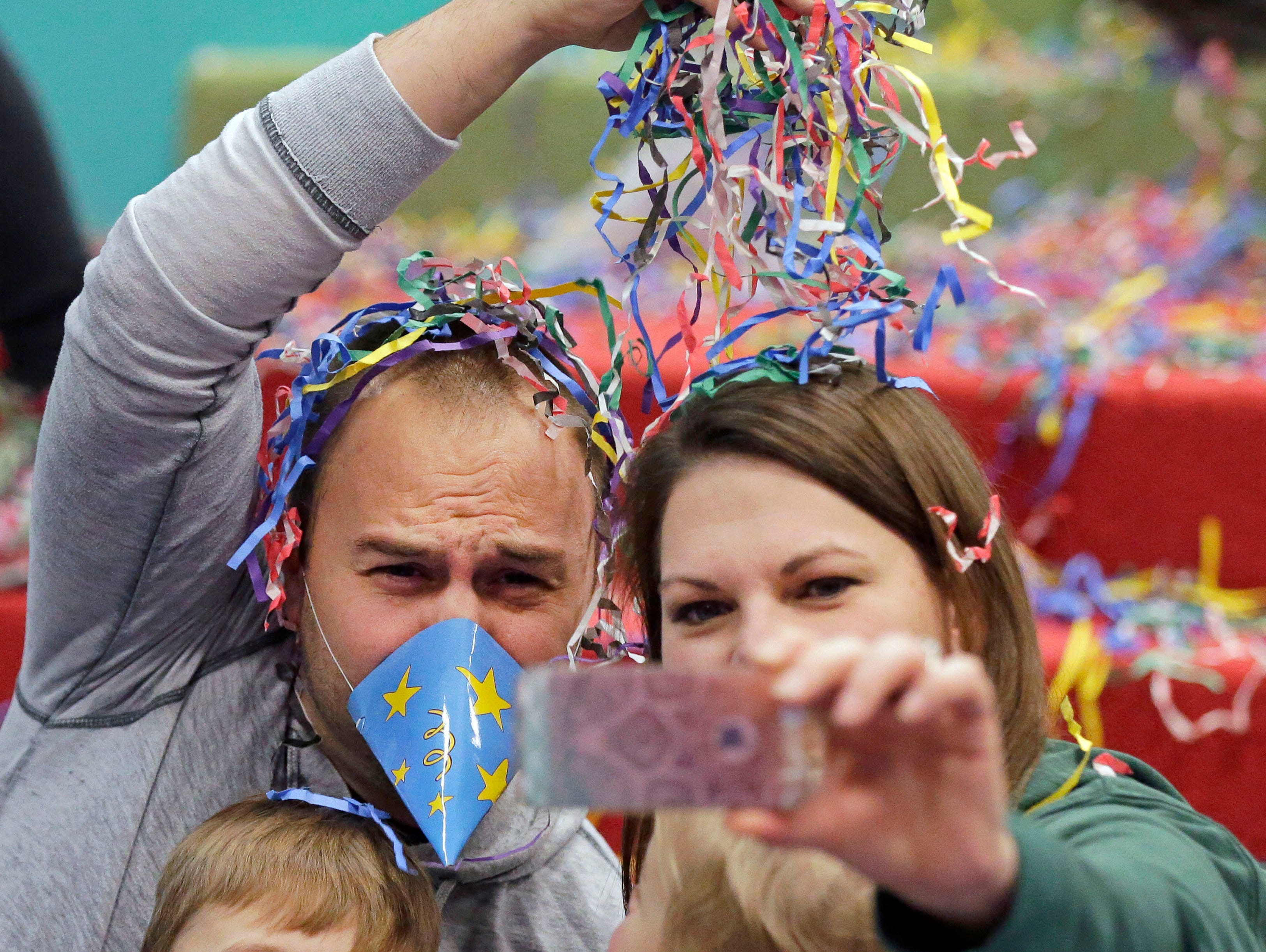 Jeff and Amanda Braunreiter of Appleton get a photo with their children Jack and Emerson following the Noodles Around the World New Year's Eve celebration at The Building for Kids Children's Museum Sunday, December 31, 2017, in Appleton, Wis.