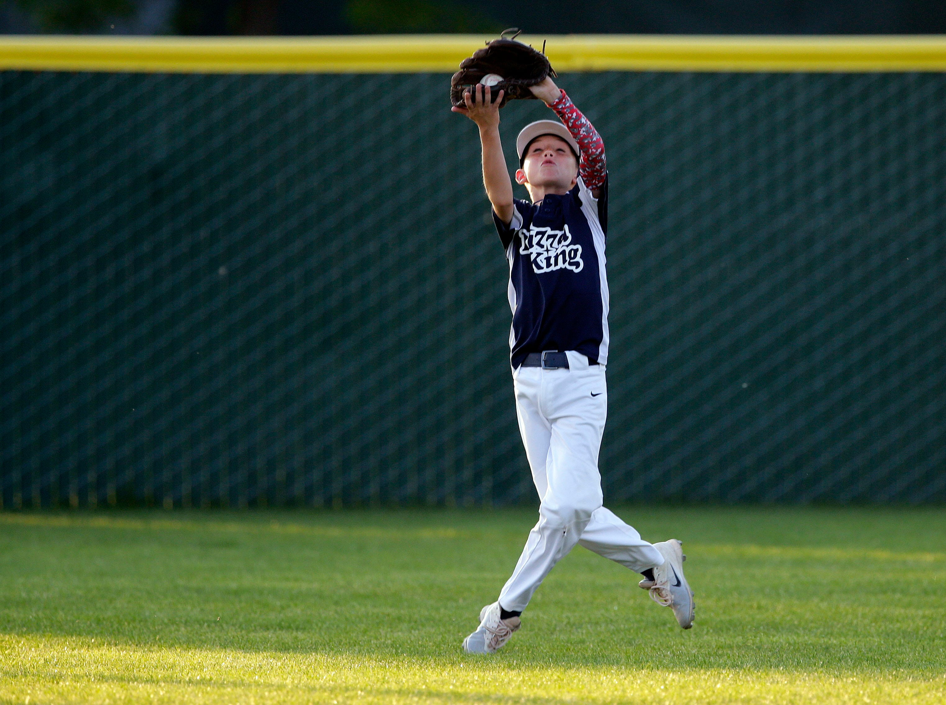 Eli Vezina of Pizza King makes a catch in the outfield as the Appleton Little League baseball and softball championship games take place Wednesday, June 27, 2018, at Scheels USA Sports Complex in Appleton, Wis.
