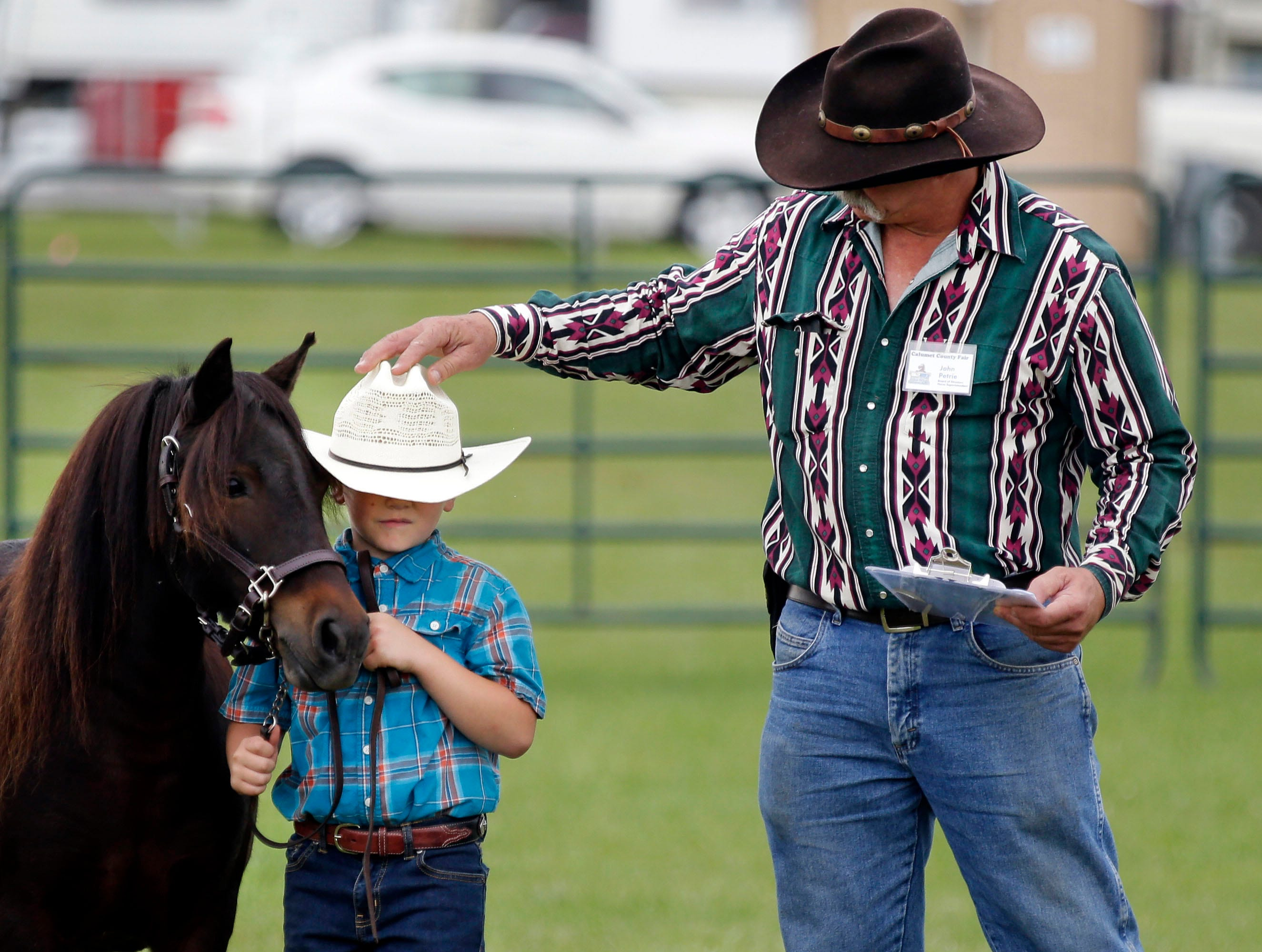 John Petrie, right, returns a hat to Salvatore Alloy after his horse, Brownie, brushed it off during the Pony Halter judging at the Calumet County Fair Saturday, September 1, 2018, in Chilton, Wis.